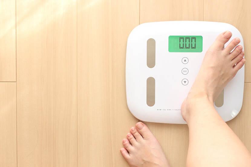 体重計に乗って体重と体脂肪率をはかる